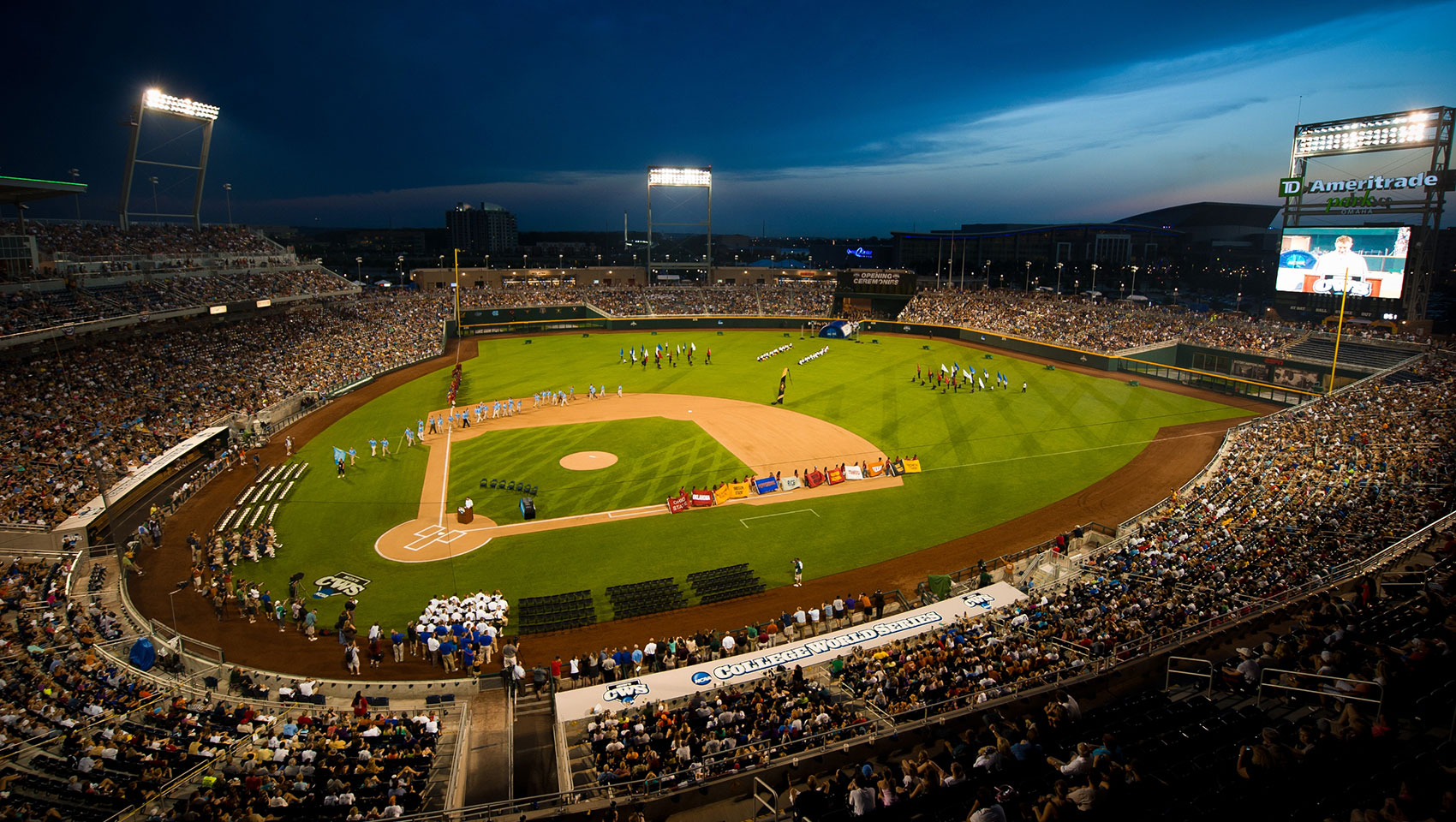 baseball stadium at dusk with teams on the field